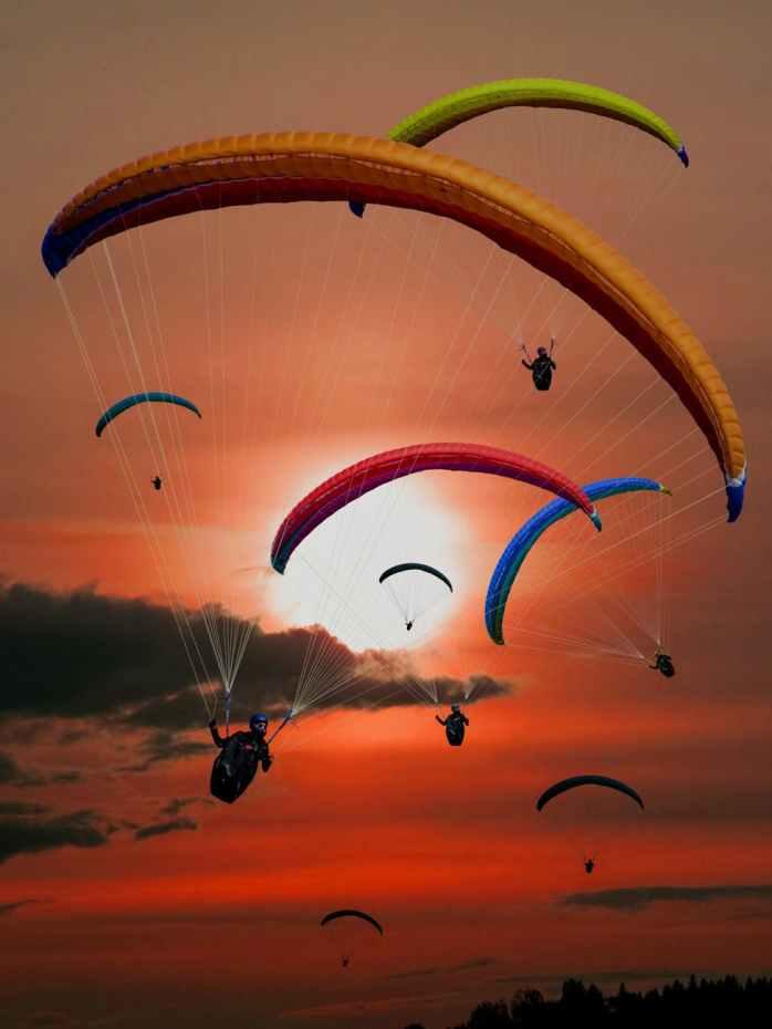 people riding parachutes during sunset