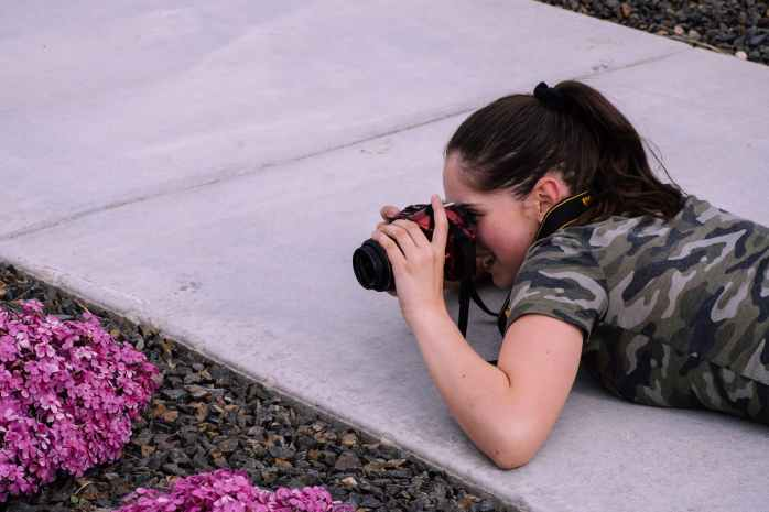 woman lying on pavement while taking photo