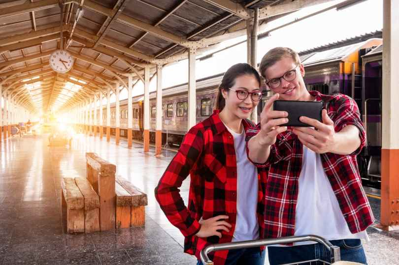 man and woman taking selfie near gray train