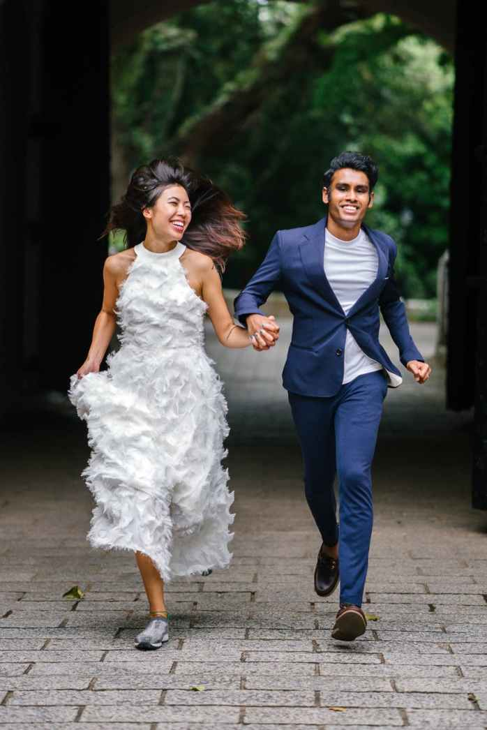 bride and groom running on concrete pathway
