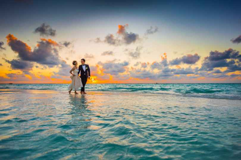 man and woman walking of body of water