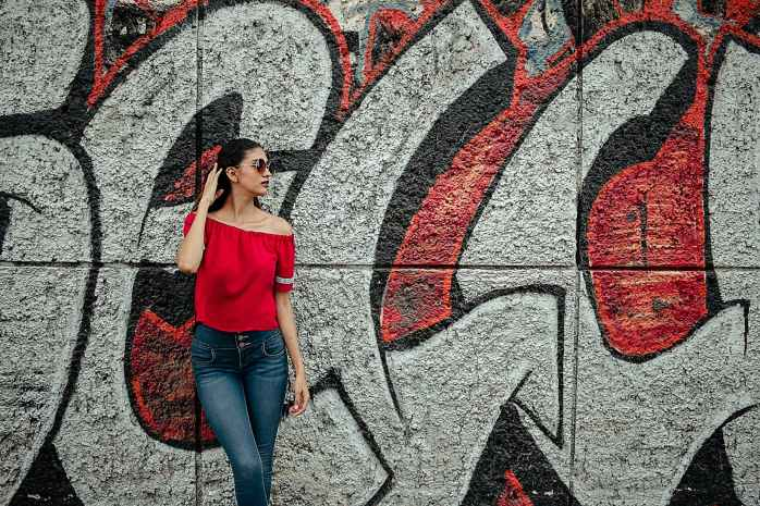 woman wearing red off shoulder shirt and blue denim stone wash jeans near red and gray graffiti wall