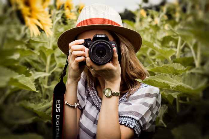 selective focus photography of woman holding dslr camera